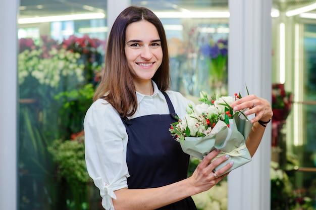 Владелец цветочного магазина делает букет из белых роз