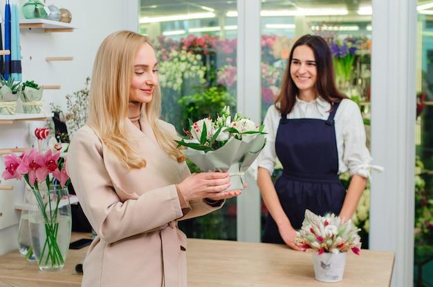 Владелец цветочного магазина продает букет белых роз покупателю