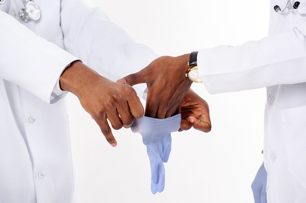 Африканские доктора на изолированной белизне с фонендоскопом надели медицинские перчатки.