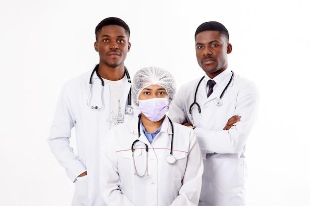 Три доктора на белом. индийская женщина с стетоскоп. африканские мужчины.