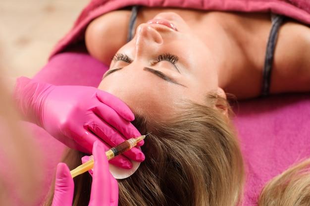 美容師が女性の頭にコラーゲンを注入