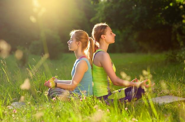Девушки позируют йогу на улице в лесу утром