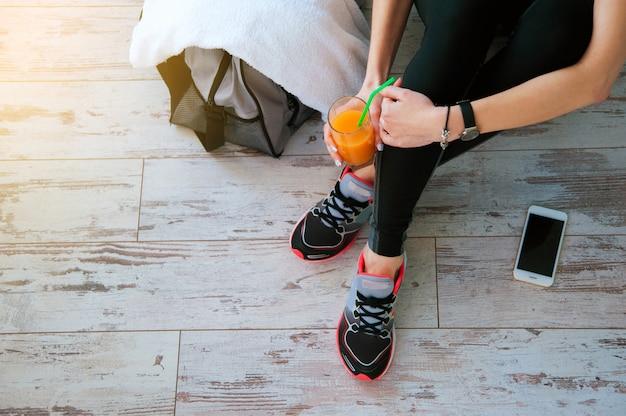 Женщина с сидя на полу со стаканом апельсинового сока после спорта