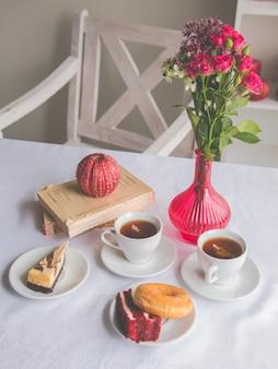 Крупный план сервировки блюд на столе: чай, пончик, кусок торта, цветы в вазе, свечи, книги