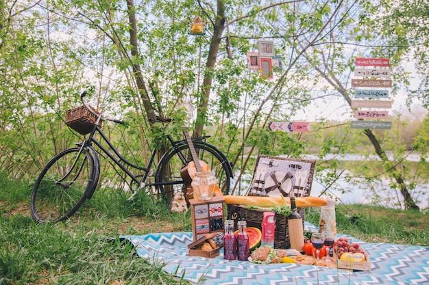 自然の中で夏のピクニックをデザインします。格子縞の上に食べ物のバスケットがあります。