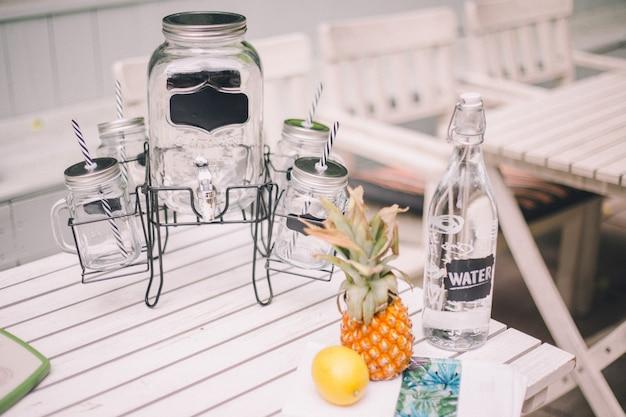 レモン梨レモネードとレモネード。近くにはボトル、レモン、パイナップルの装飾があります。