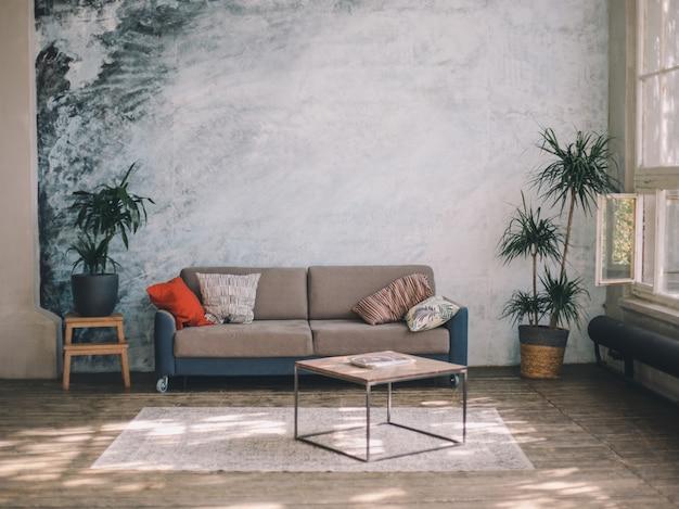 インテリア・デザイン。水色の壁とフローリングの床に対する家具