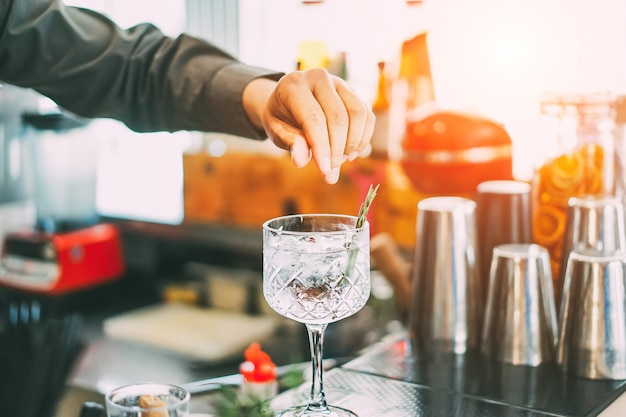 バーテンダーが夕暮れ時の屋外でアメリカのバーでクリスタルグラスのカクテルと芳香のハーブ