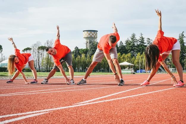 屋外で一緒にトレーニング若いランナーを実行する前に足を伸ばしてスポーティな友人