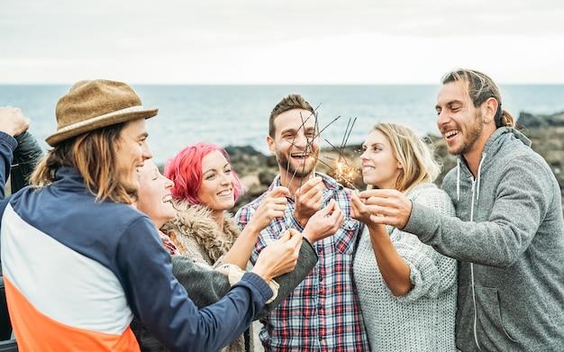 Счастливая группа друзей празднует с сверкающими звездами фейерверк на открытом воздухе