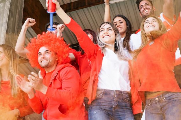 スタジアムでサッカーの世界の試合を見ているサッカーサポーターファン
