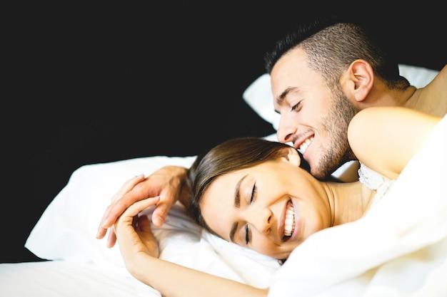 彼らの新婚旅行でベッドに横たわっている恋人たちの若いセクシーなカップル