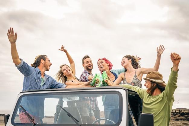 コンバーチブル車でビールで応援して幸せな友人のグループ