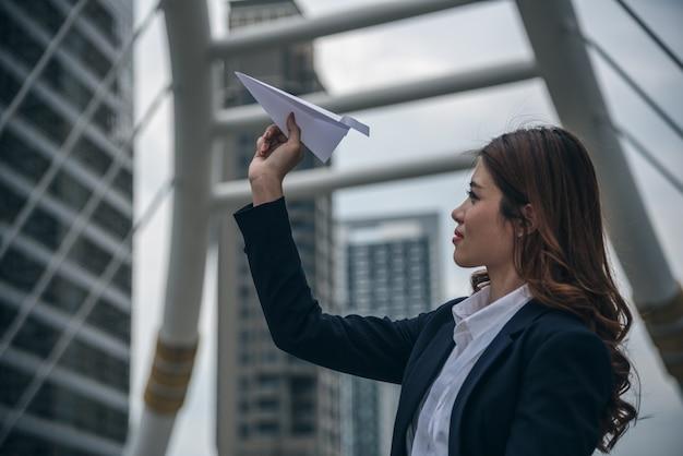 Портреты красивой азиатской женщины выглядят уверенно стоять и держать бумажный самолетик