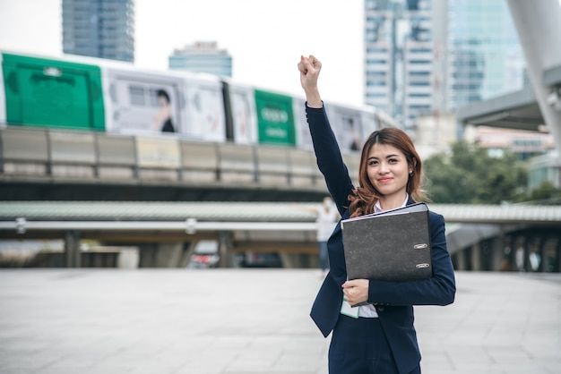 美しいアジアの女性の肖像画は陽気で見て、自信は立っており、成功を感じている