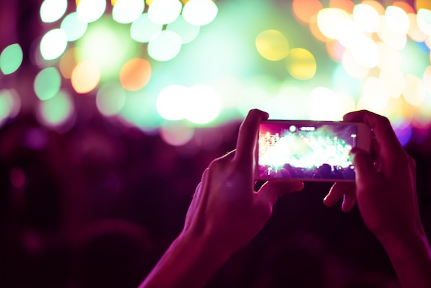 スマートフォンを持っている手のぼんやりしたカラフルな背景は、写真の人々がコンサートで混雑している。