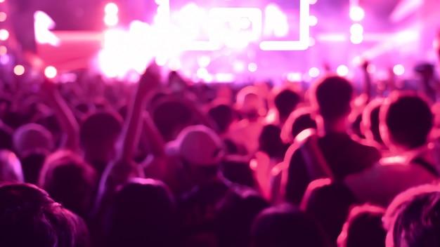公共のコンサートで抽象的なカラフルな背景の観客。
