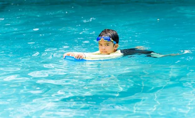 Симпатичный мальчик учится плавать в бассейне