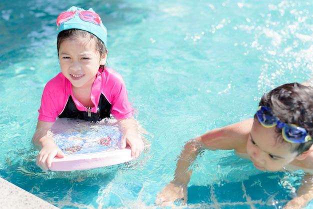 Довольно маленькая девочка плавает в открытом бассейне и веселится со своим другом