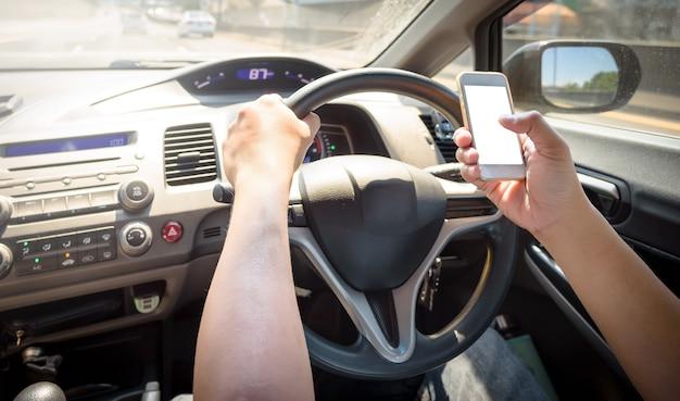 高速道路で車を運転しているときに携帯電話を使っている男