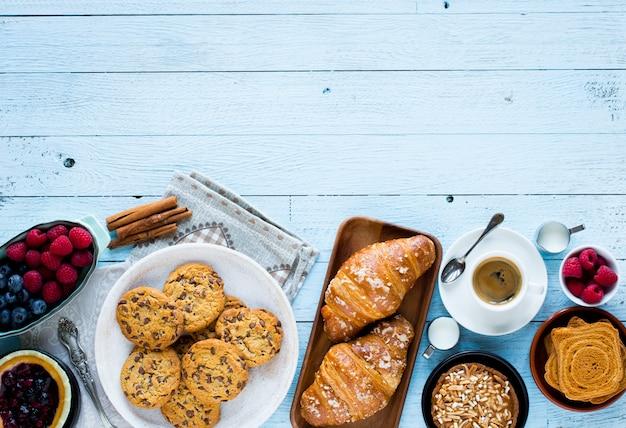 Вид сверху деревянный стол, полный тортов, фруктов, кофе, печенья, специй и многое другое