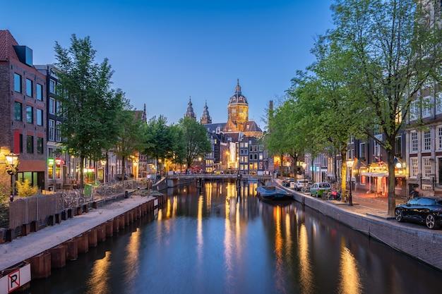 オランダ、アムステルダムの夜の聖ニコラス教会とアムステルダム市内の夜