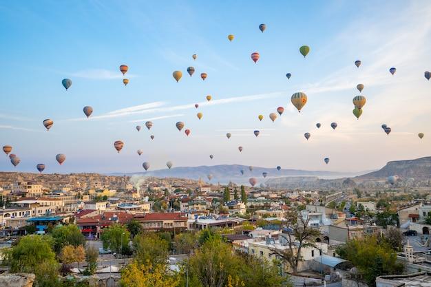 Горизонт города каппадокии с горячим воздушным шаром едут в небе.