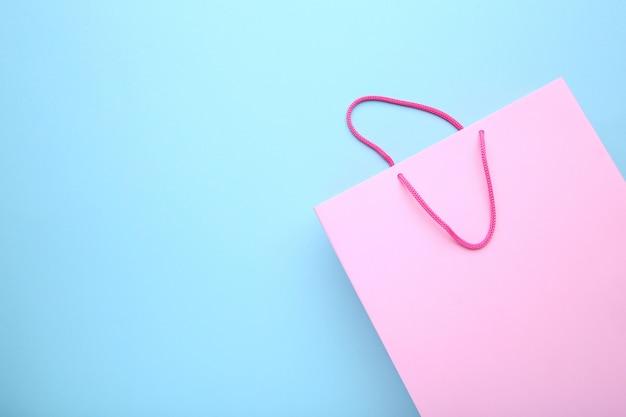 青色の背景にピンクの紙の買い物袋
