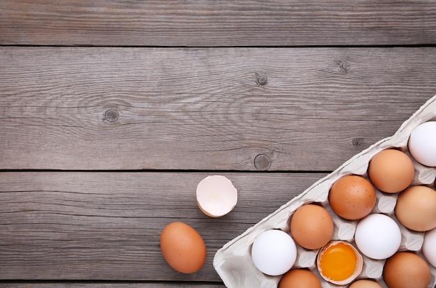 鶏の卵は他の卵の中で半分壊れています。灰色の木製の背景上のコンテナーに鶏の卵