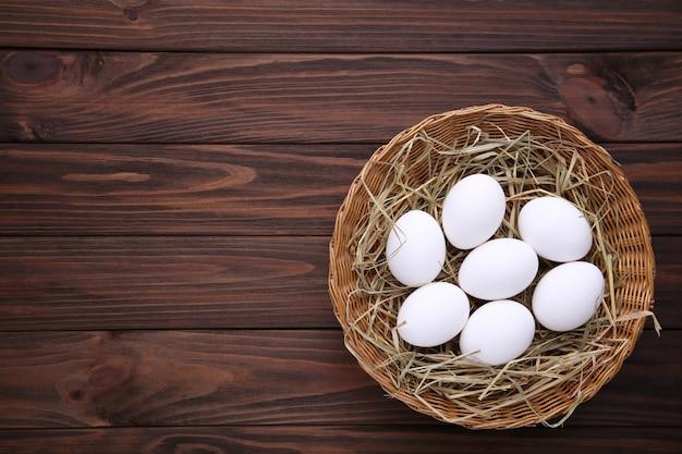 茶色の木製の背景にバスケットで新鮮な鶏の卵