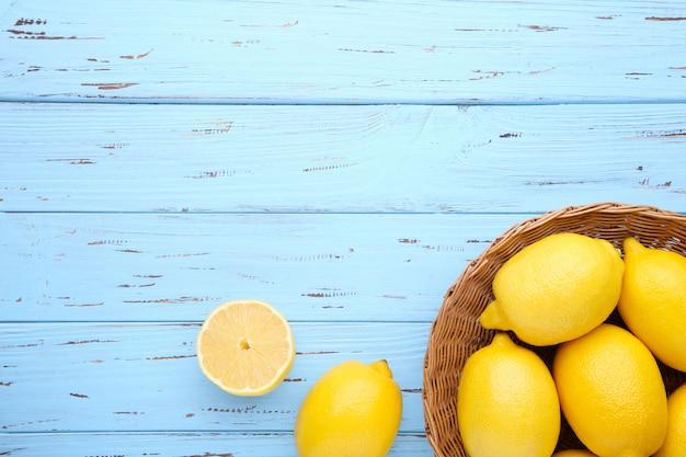 青の背景にバスケットで分離されたレモン。トロピカルフルーツ。