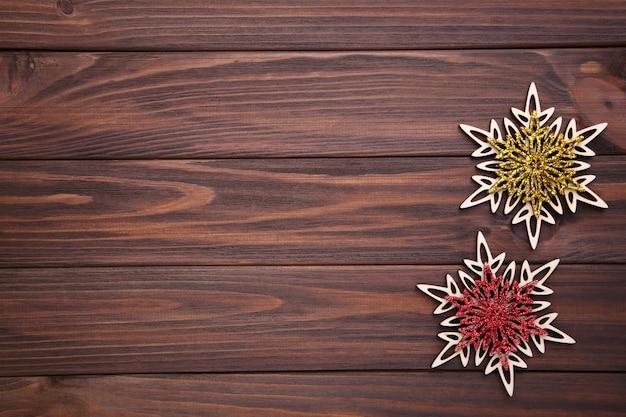 茶色の木製の背景に雪の結晶。クリスマスのコンセプト。