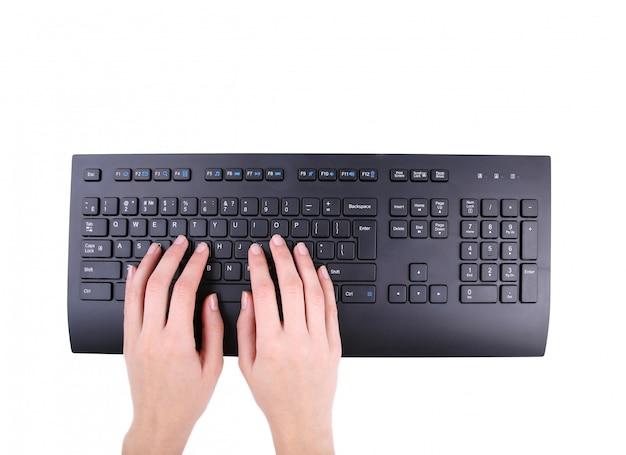Женские руки или женщина офисный работник, набрав на черной клавиатуре, изолированные на белом