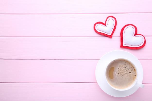 バレンタインの日、ピンクのテーブルの上の心とコーヒーのカップ