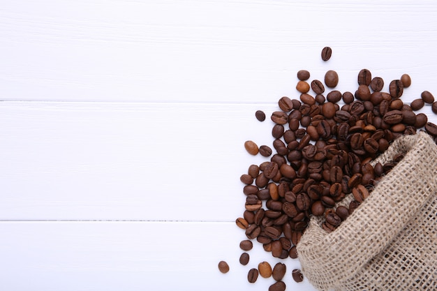 白いテーブルの黄麻布の袋のコーヒー豆