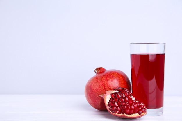 灰色の背景に熟したザクロとフルーツジュースのグラス