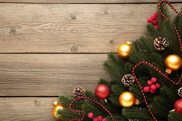 Рождественские украшения. еловая ветка с красными и золотыми шарами на сером фоне