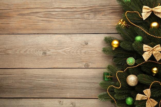 Рождественские украшения. еловая ветка с зелеными и золотыми шариками на сером фоне