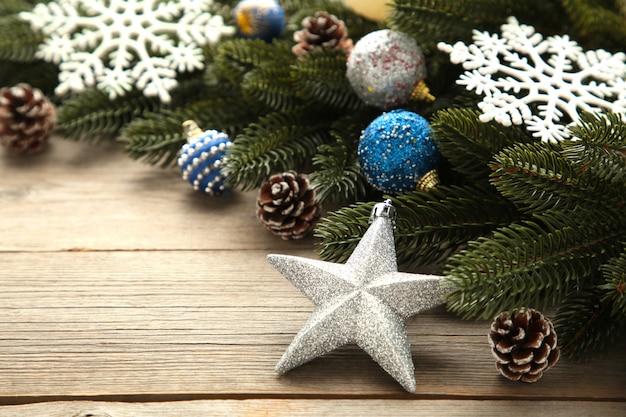Еловые ветки с серебряными и синими новогодними украшениями на сером фоне