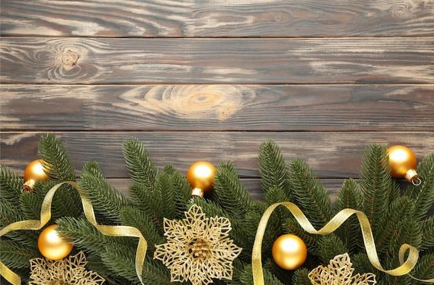 Рождественские украшения. еловая ветка с золотыми шарами, рождественские цветы и ленты на коричневом