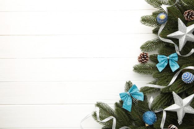Еловые ветки с серебряными и синими рождественскими украшениями на белом фоне