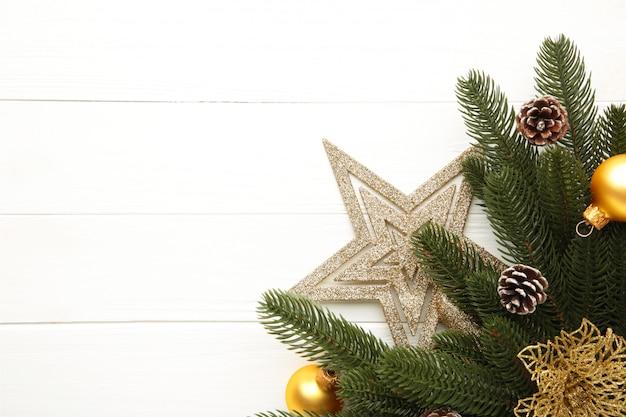 クリスマスの飾り。金の星、クリスマスの花、白のボールとモミの木の枝