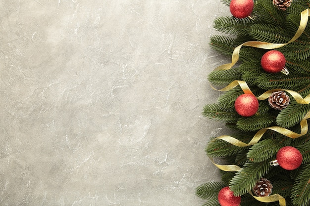 Рождественские украшения. еловая ветка с золотыми шарами и лентой на сером фоне бетона