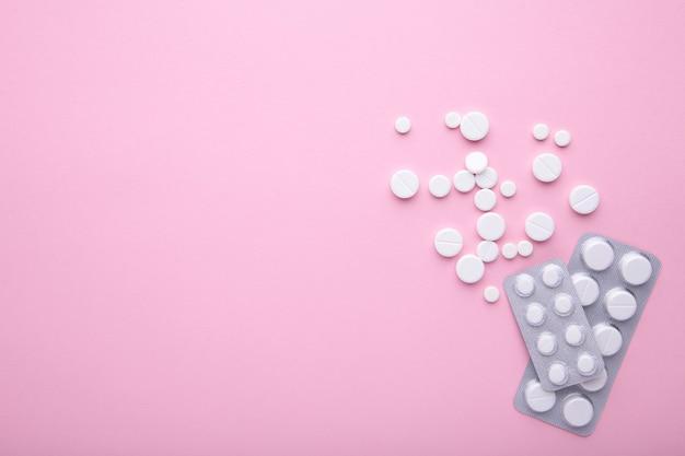 Белые таблетки на розовом фоне с копией пространства