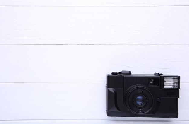 白い木製のテーブルにビンテージカメラ。古い写真カメラ
