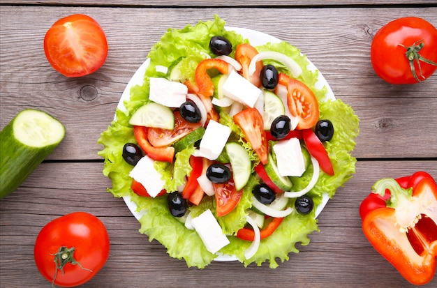灰色の木製テーブルに野菜と新鮮なギリシャ風サラダ