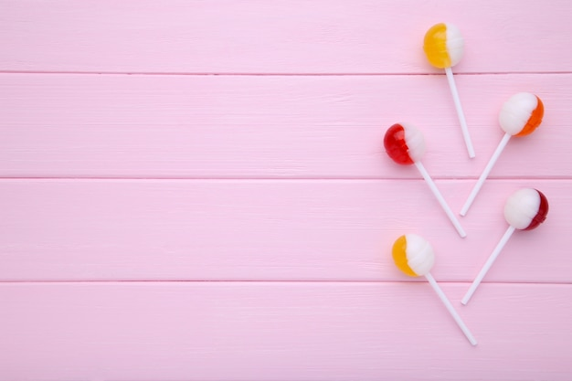 ピンクのテーブルの上のロリポップ。甘いお菓子のコンセプト
