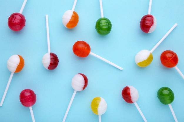青いテーブルに多くのカラフルなロリポップ。甘いお菓子のコンセプト