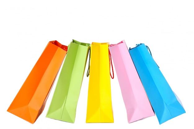 白で隔離されるカラフルな紙のショッピングバッグ