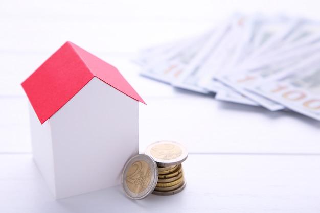Дом из белой бумаги с красной крышей, с монетами на белом фоне